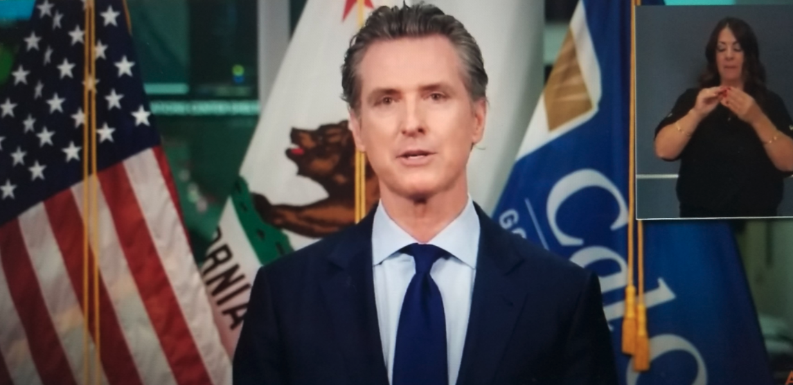 Governor Newsom standing in front of three flags with gold rope extending from top for each one - US, Cali and one other