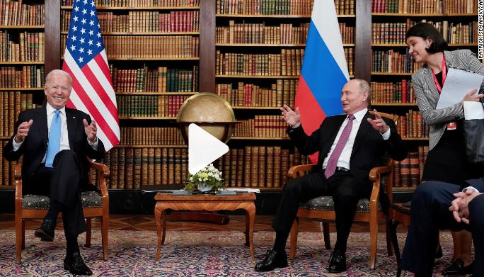 Biden and putin seated with country flags beside them