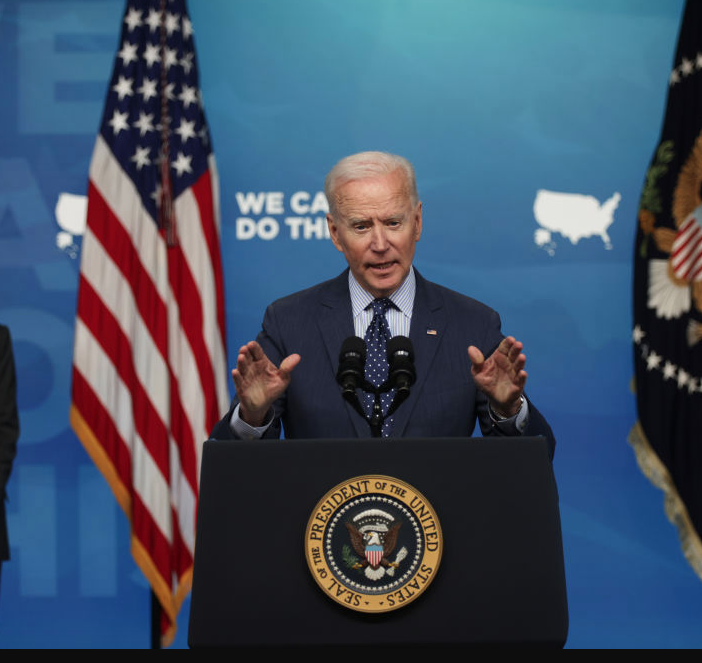 Biden standing in front of flag with gold trim