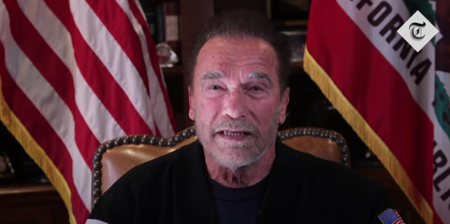 Arnold Schwarzenegger speaks in front of gold-trimmed flags for US and State of California